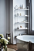 Shelf with bathing utensils, freestanding bathtub in front
