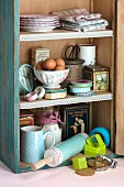 Utensils, eggs and flour in kitchen cabinet