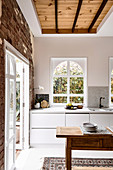 Arched window in the kitchen with brick wall and wooden table
