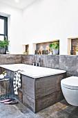 A bath tub with large format, concrete-style tiles
