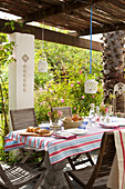 Set table on roofed terrace in summer garden