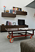 Coffee table on castors, TV on sideboard and wall-mounted shelves in industrial loft apartment