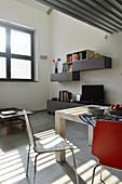 Essbereich mit Designerstühlen, Sideboard mit Fernseher und Wandregal im Industrie-Loft