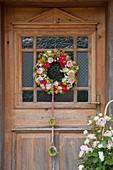 Kranz aus Rosen und Frauenmantel an Haustür