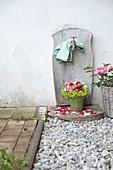 Rosenstrauss mit Frauenmantel und Obstblüten und Blumenkorb mit Rosen am Brunnen
