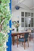 Blick auf Esstisch mit Armlehnstühlen und Designerleuchte in offenem Wohnraum
