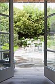 Blick auf Terrasse mit Tisch, Stühlen und Hund, umgeben von sommerlichem Garten
