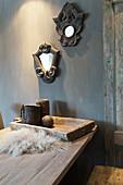 Zwei Spiegel mit opulenten Rahmen an grauer Wand über dem Holztisch