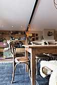 Wooden dining table and chairs on black-tiled floor in converted barn