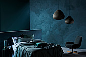 Double bed and armchair in the bedroom with dark blue walls