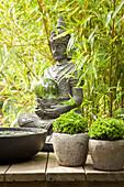 Seated Buddha statue amongst bamboo