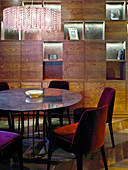 Round table and upholstered chairs in front of dark fitted cabinets