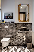 Patterned floor reflected in glossy stone wall cladding in bathroom