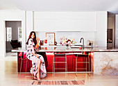 Young woman sits at elegant kitchen counter with marble countertop and red front