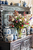 Lavish flower arrangement and vases on antique dresser with ornate carved front