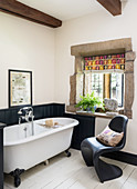Free-standing bathtub and black classic chair in rustic bathroom