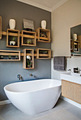 Shelves made from wooden crates on grey wall in bathroom