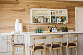 White counter in front of wall-mounted shelving with mirrored back wall used as bar cabinet