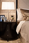 Lamp and photos on stylish bedside cabinet with drawers