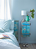Vintage closets in turquoise as bedside table next to bed with wooden headboard in matching color