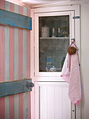 View through pink and white painted wooden door on display cabinet with kitchen utensils
