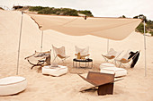 Table, seat cushion and butterfly chairs under shade sail in the sand