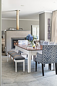 Bench with seat cushion, chairs with various upholstery in open-plan dining room