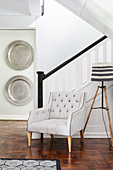 Armchair and standard lamp at foot of staircase with silver platters decorating wall in background