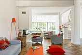 Offenes Wohnzimmer mit grauen Polstermöbeln und roten Akzenten