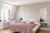 Pink blanket on bed flanked by niches instead of bedside tables