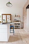 weiße Kücheninsel und blauer Barhocker in offener Küche mit Holzdielenboden und Ziegelwand