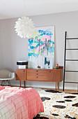 Abstraktes Gemälde auf dem Retro-Sideboard im Schlafzimmer