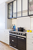 Glass and steel wall units above vintage-style cooker