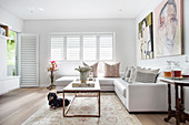 White leather corner sofa and coffee table with marble top in bright living room