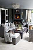 Lounge furniture and fitted fireplace on roofed terrace in shades of grey