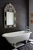 Free-standing bathtub below mirror on dark grey wall