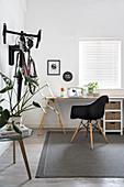 Arbeitszimmer mit schlichtem Schreibtisch und Klassikerstuhl, Fahrrad an der Wand