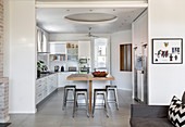 Wooden counter and barstools in white fitted kitchen