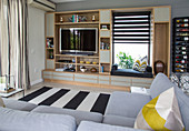 Fitted shelving with TV and integrated windows seat, black and white striped rug and pale grey corner sofa in living room