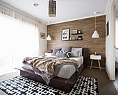 Earth-colored bedroom with wood-clad wall