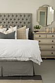 Double bed with button-tufted headboard, chest of drawers and wall-mounted mirror