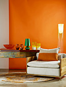 Wood-framed armchair, designer standard lamp and glass vases on console table against orange wall