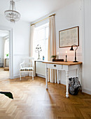 Table with drawer and chair in corner of period apartment with herringbone parquet floor and white walls