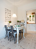 Metal chairs around white dining table below wall decal