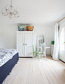 White wardrobe, round table and chair and double bed in bedroom with pale wooden floor