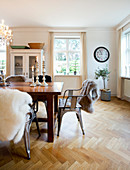 Sheepskins on metal chairs around wooden table in dining room