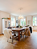 Wooden table and classic chairs with sheepskin rugs in dining room with herringbone parquet floor