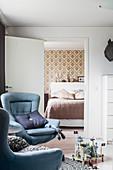 Zwei blaue Sessel vor der offenen Tür zum Schlafzimmer