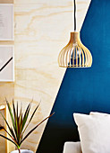 Pendant lamp in front of plywood wall with a blue, geometric pattern