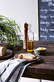 Olive oil, cheese and bread on rustic wooden table